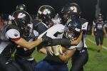 Huntington North High School football players (from left) Jackson Holzinger, Lawson Shearer and Michael Kline tackle Norwell High School football player Isaiah Brege on Friday, Oct. 9, during the HNHS Homecoming football game. The Vikings fell to the Norwell Knights 30-14.