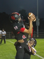 Huntington North wide receiver Scott McClellan (left) makes a catch in the end zone while draped by a defender during the varsity football team's game against visiting Marion on Homecoming Night, Friday, Sept. 27.