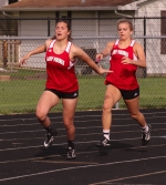 Josie Graft (right) reaches the baton out to Katie McQuinn  on an exchange in the 400-meter relay in a home three-way girls' track meet on Tuesday, April 18.