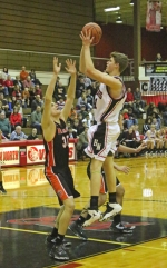Huntington North's Mitchell Geller (right) fires a jumper in the first half of a boys' varsity basketball game versus Warsaw on Saturday, Dec. 3, in North Arena. The Vikings pushed the fifth-ranked Tigers hard, but came up short, 44-40, in overtime.