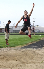 Mohamed Almalahi flies through the air on his way to winning the junior varsity long jump competition during a three-way meet the Huntington North High School boys' varsity track team hosted against Leo and DeKalb.