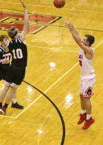 Trey Williams (right), a junior on the Huntington North High School boys' varsity basketball team, fires a shot from three-point land over Southwood's Dallas Holmes during a game on Friday, Dec. 1, at North Arena. The Vikings held on for a 49-46 win.