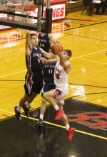 Huntington North guard Zach Daugherty takes the ball to the hoop with his left hand against a pair of Bellmont defenders in action Saturday night at North Arena. The Vikings blew out the Braves, 77-41.