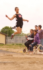 Huntington North senior Ricky Haught tries to get a little more distance on his long jump during the New Haven Boys Track Sectional on Thursday, May 16. Haught finished second to advance to regional.