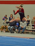 Huntington North senior Aleah Eckert splits in mid-air during her floor exercise performance at the Huntington North Regional Gymnastics Tournament on Saturday, March 7.