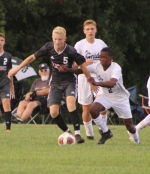 Peyton Miller (left), a senior on the Huntington North High School boys' soccer team, encounters resistance from Snider's Nigel Bond as he maneuvers with the ball during the Vikings' season-opening game on Tuesday, Aug. 20, at Huntington North. The Vikings lost, 2-0.