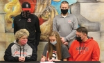 Huntington North High School senior Grace Gross (bottom row, middle) signs a letter of intent to compete on the Grace College track team while her parents Jenny Gross (bottom row, left) and Tom Gross (bottom row, right) as well as Grace College track coach Max Kittle (top row, left) and HNHS track coach Brian Milton (top row, right) look on. Grace signed with the college on Thursday, Jan. 7.