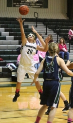 A masked Amelia Recker tosses the ball in for two of her 12 points during a game between her Huntington University Foresters and visiting Mount Vernon Nazarene University on Saturday, Feb. 13. Playing in front of their eighth-annual Pink Out crowd, the Foresters won big, 70-54.