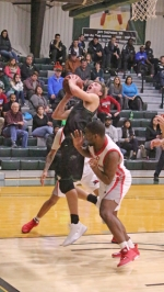 Mason Coverstone (left), a junior on the Huntington University men's basketball team, twists around a pair of defenders as he elevates for a layup during a game against visiting Indiana University Northwest in the Ness Bros. Hall of Fame Tournament on Friday, Nov. 10. The Foresters beat the Redhawks, 99-92.