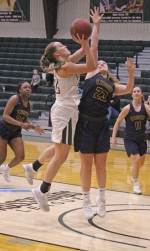Huntington University forward Brooke Saylor goes up for a shot over Marian's Karen Jones near the hoop in play Saturday afternoon, Jan. 13, at Platt Arena. The Foresters lost by a point, 61-60.