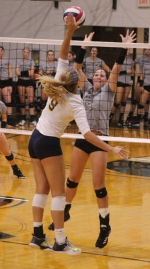 Danielle Gurwell (right), a senior on the Huntington University volleyball team, sticks her hands up to block a scoring attempt by Hannah Trout during a match against visiting Marian University on Saturday, Sept. 23. The Foresters got edged by the Knights, 2-3.