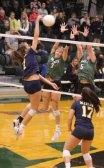 Huntington University volleyball players Tailor Schultheis (left) and Lindsay Ingenito try to stop a Marian attack in action Saturday, Oct. 27, at Platt Arena.