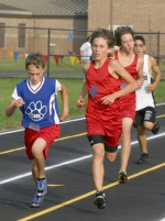 Crestview Middle School's Alec Justice (left) overtakes two runners from Marion Justice Middle School during the final stretch of the course to win the seventh grade cross-country race at the Riverview Invitational on Saturday, Sept. 12.