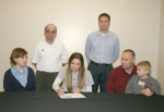 Huntington North High School senior Whitney Neuenschwander (front center) signs a letter of intent to play tennis at Bethel College on Tuesday, March 24.