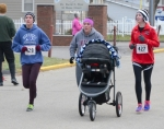 Flanked by sisters Mariah Patrick (left) and Kayla Patrick (right), Tyffany McWhorter pushes a baby stroller containing her 7-month-old son, Everett, toward the finish line near the end of the 10th annual Pathfinder Kids Kampus Turkey Trot on Thanksgiving, Nov. 27, in Huntington. McWhorter reported the child slept throughout the race.