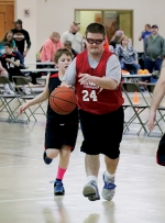Trevor Whitesell (middle), a Pathfinder Community Supports client, dribbles a basketball during a Special Olympics Basketball event at Taylor University, in Upland, on Saturday, March 21. To Whitesell's left is teammate Jameson Peters.