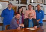 Ben Davis (seated at left), executive director of the Parkview Huntington Family YMCA, and Huntington Mayor Brooks Fetters (seated at right) recently signed an agreement to merge the youth soccer programs that had been operated separately by the YMCA and the Huntington Parks and Recreation Department. With them are (standing, from left) Steve Yoder, assistant superintendent of the Parks Department; Allison Timbrook, the city's community engagement volunteer coordinator; and Tim Allen and Rob Miller, youth sports directors at the YMCA.