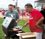 Mike Schnitz (right) grills hotdogs as Jeff McCutcheon takes finished ones so they can be prepared and served to attendees of last year's Ultimate Tailgate Party outside Kriegbaum Field in Huntington.