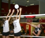 Lady Viking Melissa Grossman (right) follows through on her spike against the efforts of Snider's Emily Smith (left) and Somer Johnson in varsity volleyball action on Tuesday, Sept. 8. The Lady Vikings lost in five sets.