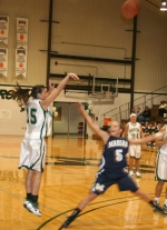 Huntington University guard Sarah Miller launches a 3-pointer despite the defensive efforts of Marian's Emily Smithson in the Foresters 67-54 win on Saturday, Feb. 20.