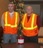 Ron Eckert (left) and Tony Godfroy stand in the reflective vests that they and other members of the Huntington Council of the Knights of Columbus will be wearing on Saturday, Dec. 8, as part of the 2012 Pitch-In roadblock.