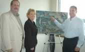 Huntington Mayor Steve Updike, Huntington County Commissioner Kathy Branham and Jaime Miller, treasurer of the Huntington Board of Aviation, (from left) stand next to a map showing a road that will be extended to provide emergency access.
