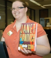 "Jessi Brown holds up a copy of Janet Evanovich's ""Four to Score,"" the adult fiction title most borrowed at the Huntington City-Township Pulbic Library in 2008."