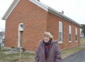 Jean Gernand stands in front of the restored German School on CR 1000W, Huntington County, IN.