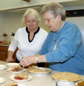 Dana Flora (left), president of the St. Mary Rosary Sodalilty, and member Marcy Wall prepare pie to be served at a recent meeting of the organization.