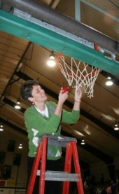 Huntington University women's basketball team coach, Lori Culler, cuts down a piece of the net after HU beat Taylor last Monday night, March 2, to win the Mid-Central College Conference Tournament crown.