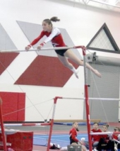 Huntington North High School varsity gymnast Olivia Eckert performs her routine on the uneven bars during the team's meet against Elmhurst and South Side on Wednesday, Feb. 25.