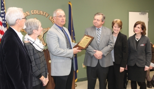 Ed Reuter (third from left), executive director of the Statewide 911 Board, presents the family of J. Edward Roush with a plaque commemorating 50 years of 911 service Thursday, March 1, at the Huntington County Sheriff's Department. Roush, a U.S. congressman from Huntington, was instrumental in enacting the 911 system, saving countless lives nationwide. Celebrating the occasion are (from left) Paul Wright and his wife, Roush's daughter Melody Wright, of Winona Lake; Reuter; Roush's son, Joel Roush and his wife, Margaret Roush, of Huntington; and State Treasurer Kelly Mitchell.