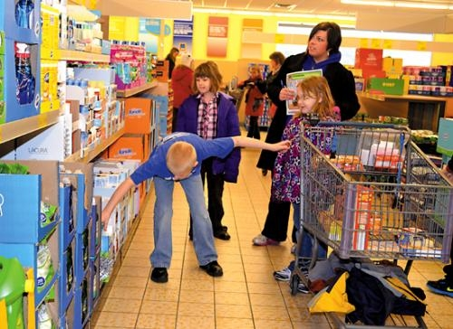Gabe Link (left), a second-grader at Andrews Elementary School, reaches for an item to place in his shopping cart at Aldi on Friday, Feb. 15. With him are classmates (from left) Ruby Kohler and Teagan Hall and his mom, Gina Link, a parent volunteer.