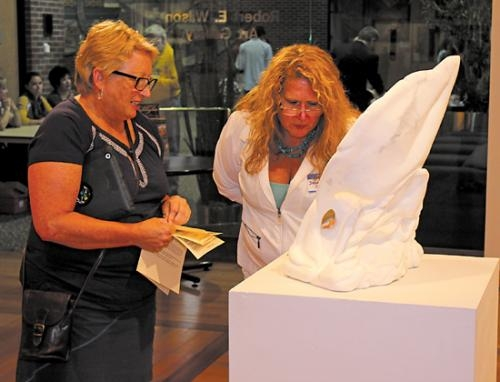 "Teri Fuller-O'Brien (left) discusses her marble sculpture entitled ""Leaves"" with Susan Stewart during the opening reception for the 2013 LaFontaine Arts Council Regional Fine Arts Show, held at the Robert E. Wilson Gallery at Huntington University."