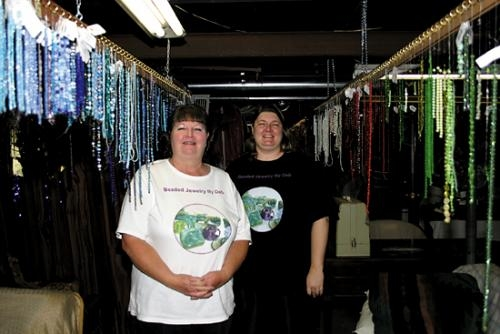 Deb Branstator (left) and Stacey Law of Beaded Jewelry by Deb, LLC are surrounded by the many strands of beads hanging in their at-home studio. Law and her mother, Branstator, opened the business in March 2012 and create handmade, one of a kind jewelry.