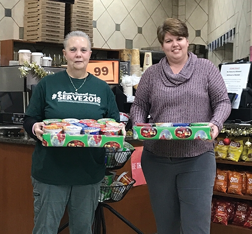 Lisa Southworth (left), manager of the Roanoke Lassus Brothers/ Handy Dandy store, presents a portion of the cereal and canned goods donated by the store's customers to Brandi Shockney, receiving the donation on behalf of Blessings in a Backpack.