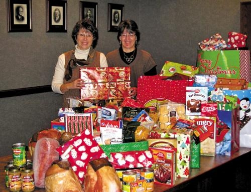 Bippus State Bank employees Dawn Downs (left) and Mari Nell Prange (right) are two of the bank employees who volunteered to shop for gifts and meals for the families adopted through Love INC. The gifts and food were delivered to Love INC on, Dec. 12.