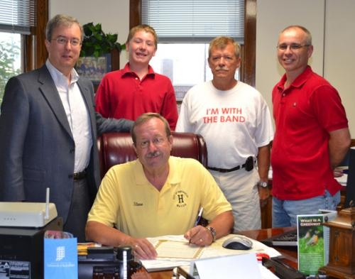 Mayor Steve Updike (seated) signs a proclamation declaring June 25-July 1 as Marching Vikes Week in the city of Huntington.