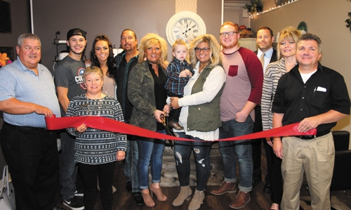 Huntington County Chamber of Commerce ambassadors join the owners, family and friends of the Beauty Bar Beautique, as they prepare to cut the ribbon to officially open the new business, located at 414 N. Jefferson St. Celebrating the occasion are (front row, from left) Steve Godfroy and Staci Mathias, chamber ambassadors; Misty Harrison, owner; Kolten Harrison, held by Kaitlyn Harrison, manager; Tyler Harrison, family member; and JoDean Knowles and Terry Miller, chamber ambassadors; and (back row, from left) John Lahr, family friend; Meriah Harrison, family member; Travis Harrison, co-owner; and Davin Smith, chamber ambassador.