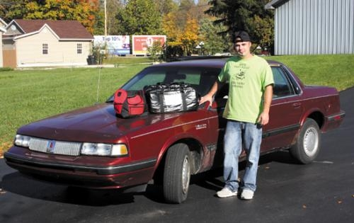 Brian Bell, owner of BB's Fastfood Delivery, in Huntington, stands with his delivery vehicle, as well as the cooler and insulated bag he uses on deliveries.