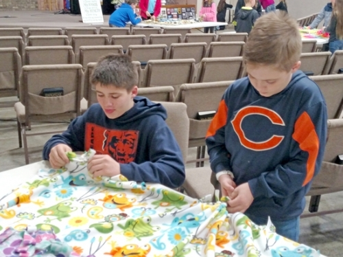 Samuel Close (left) and Charlie Close work together to make one of the 50 blankets that were part of the Wayne Township Future Farmers 4-H Club's community service projects this year.