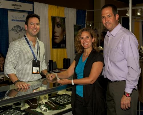 Jolene Paolillo (center) and Rob Paolillo (right) of Bowers Jewelers in Huntington, inspect merchandise at the recent Retail Jewelers Organization show in Milwaukee, WI, with a vendor.