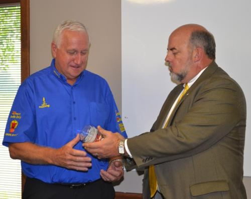 Huntington Mayor Brooks Fetters (right) hands a candy jar bearing with the seal of the city of Huntington to Auger Torque CEO Alister Rayner during a gathering on Wednesday, Aug. 21, to welcome the Australia-based company to Huntington.