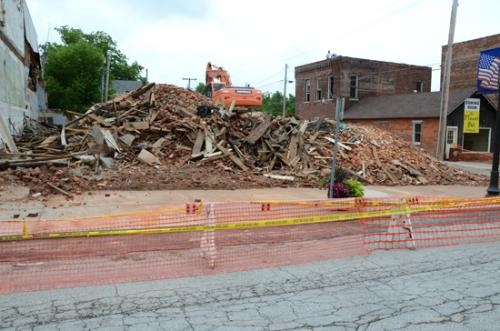 Machinery sits atop a pile of debris resulting from the demolition of the former Gene's Market and Racketty-Packetty Shop in downtown Warren.