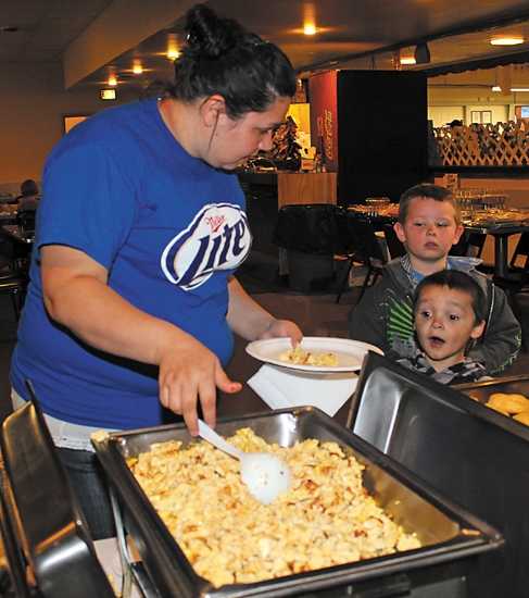 Samantha Endsley (left), a volunteer at a benefit hosted by the Fraternal Order of Eagles Post 823, in Huntington, for the Bob Burnworth family, serves her son Tristan Endsley-Medina (foreground, right) eggs on Saturday, April 6.