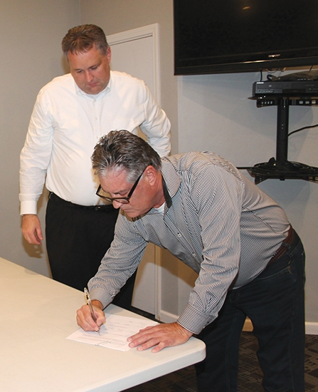 Gary Girvin (right), of Fishers and formerly of Huntington County, signs the papers donating the Draper Cabin owned by his family over to the Town of Markle, as Markle Town Council President Jeff Humbarger looks on. The cabin is expected to be ready for tours next year.