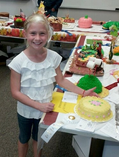Adalyn Harvey poses with her cake, which won third place in the Kid's Best Decorated (non-theme) category at the Roanoke Fall Festival cake contest.