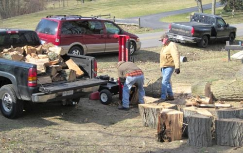 Volunteers Mike Worrell (left) and John Cass split wood from a large of tree that was cut down at the Roanoke Cemetery. They were a part of a crew from the Roanoke Lions Club and Roanoke American Legion that worked in the cemetery on April 6.