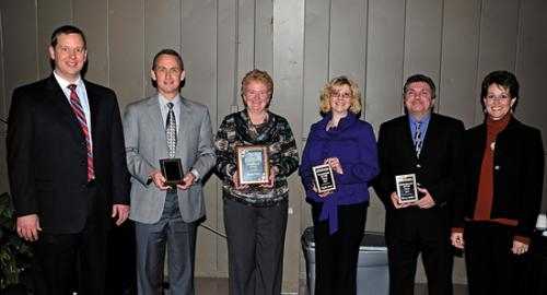 Lee Pasko (left), the 2013 Huntington County Chamber of Commerce board president, and Nicole Johnson (right) the 2012 board chairman, flank several award winners named Monday, Jan. 21, at the 2013 chamber annual dinner.