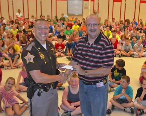 Joe Rakozcy (right), president of the Huntington Lions Club, presents a check to Chris Newton, chief deputy of the Huntington County Sheriff's Department, on Thursday, May 30, at Lancaster Elementary School.